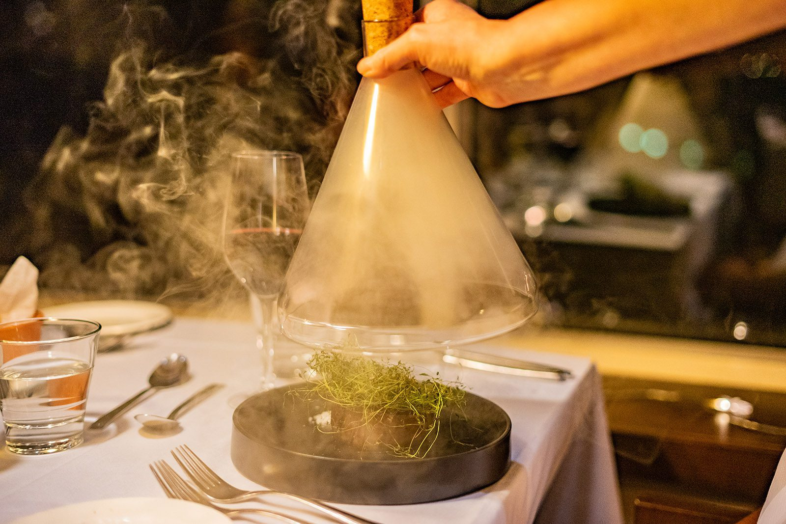 Ravintolan pöydässä tarjoilija nostaa lasisen kartion pois annoksen päältä, kartion alta tulee savua, joka ympäröi lautasella olevan pihviannoksen.