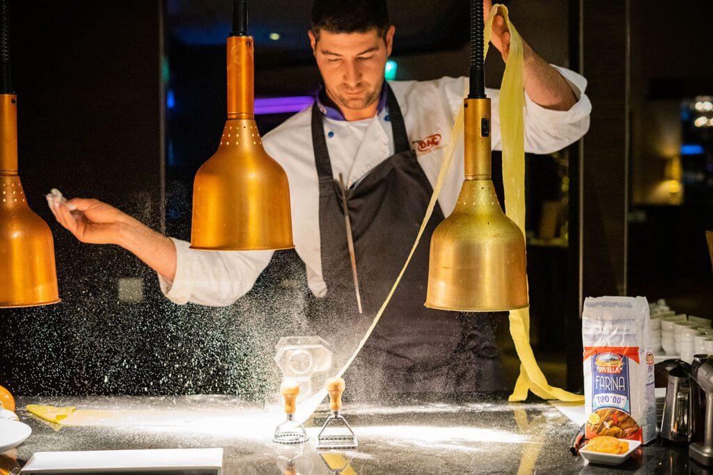 Keittiömestari Riccardo Soldati tekee pastaa keittiön pöydällä, kädessään hän pitää pastanauhaa ja toisella heittää pölyävää jauhoa taikinaan.