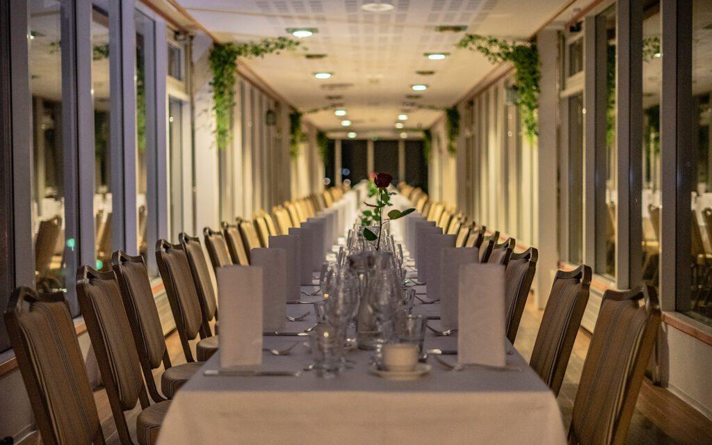 Pitkä, katettu pöytä, valkoinen pöytäliina ja ruusumaljakossa.