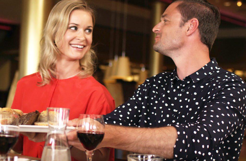 Punapaitainen nainen ja mustavalkopaitainen mies katsovat toisiaan ravintolassa ja hymyilevät toisilleen.