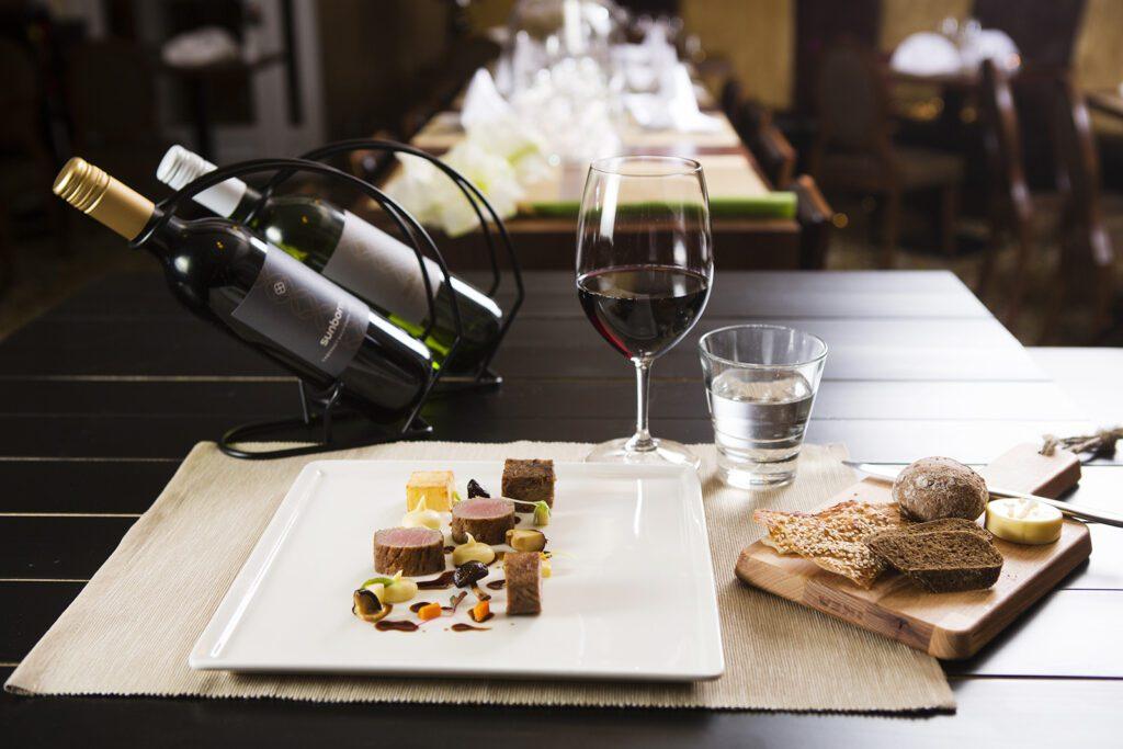 Valkoisella lautasella pihvinpaloja, kastiketta ja koristeita, puulautasella leipää. Viinilasissa punaviiniä ja kaksi Sunborn-viinipulloa telineessä pöydän päällä.