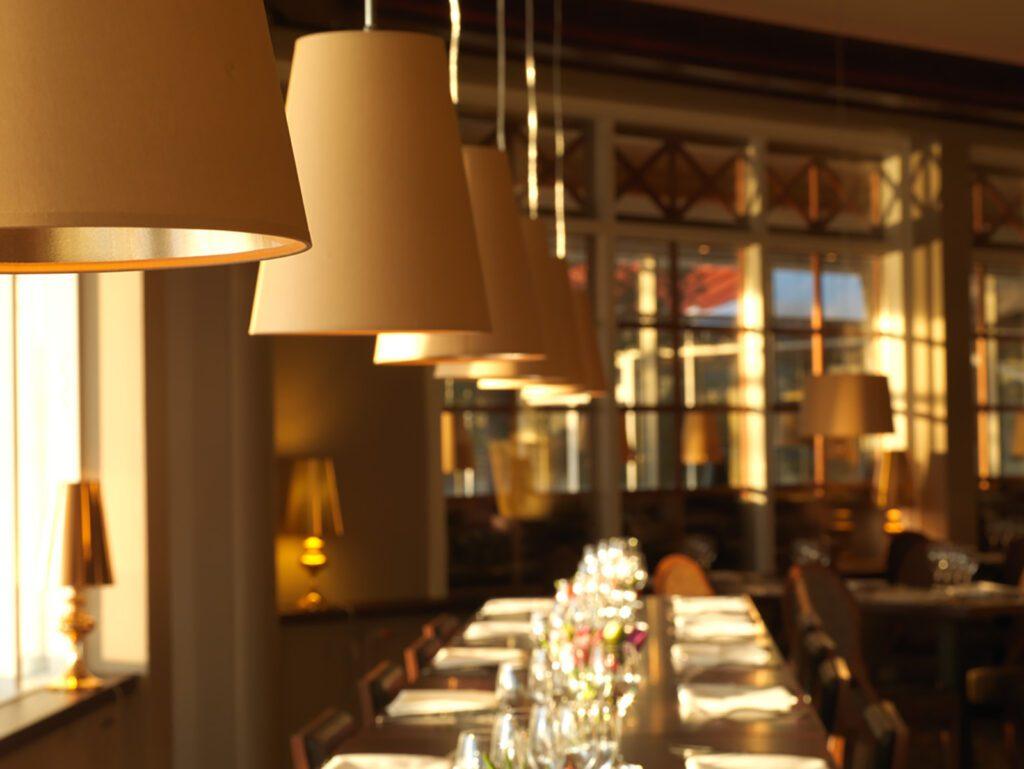 Ravintolan kultaiset lampunvarjostime roikkuvat katosta, katetun ravintolapöydän yläpuolella.