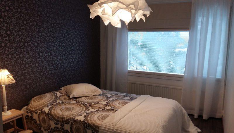 Makuuhuone, jossa vuode ja katossa valkoinen kattolamppu.
