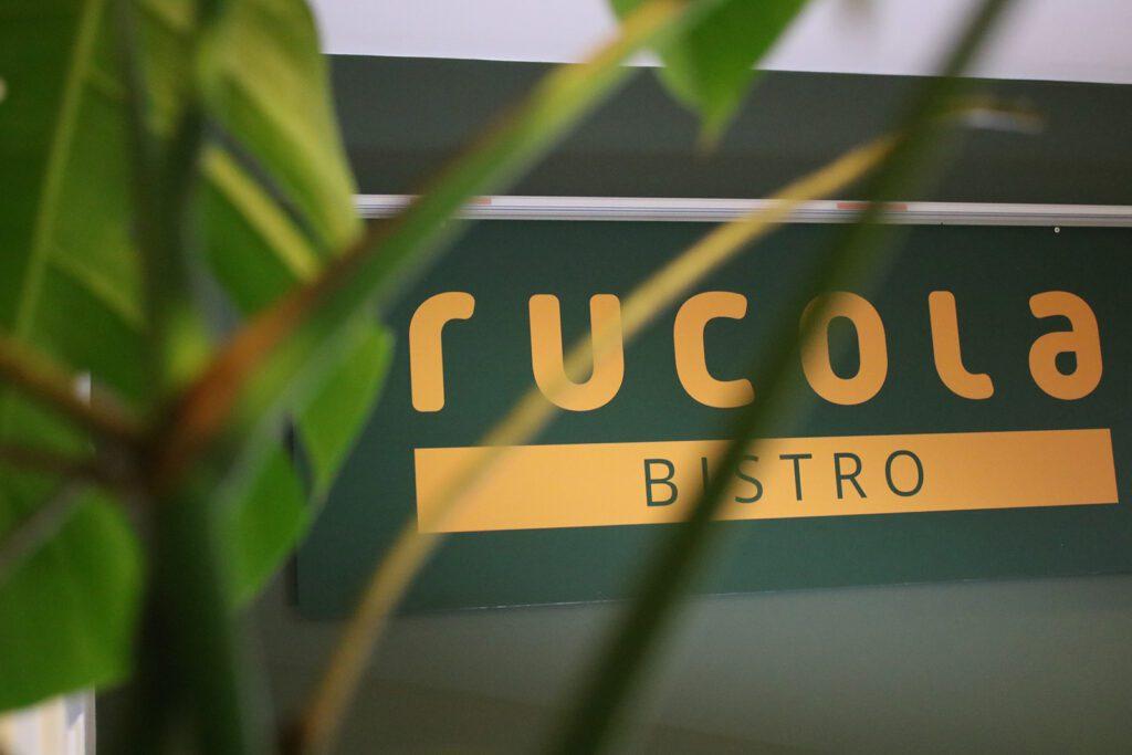 Viherkasvien läpi kuvattu kyltti, jossa lukee Rucola bistro.