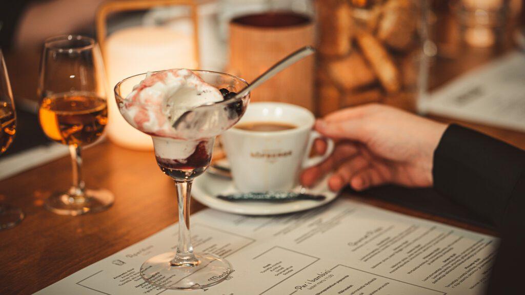 Kuva Rucola Bistron pöydästä, jossa drinkkilasissa jäätelöannos ja taustalla kahvikuppi ja digestiivi-drinkki.