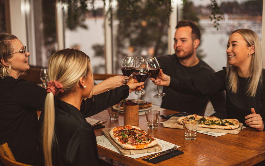 Mies ja kolme naista kilistelevät viinilaseja Rucola Bistron pöydän päällä. Heillä on edessä pitsat lankuilla.