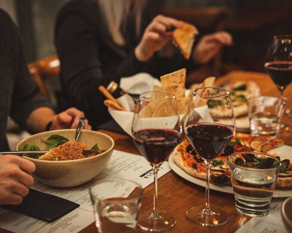 Lähikuva Rucola Bistron pöydästä, jolla kaksi punaviinilasia, pitsaa, leipää ja taustalla ruokailijotia.