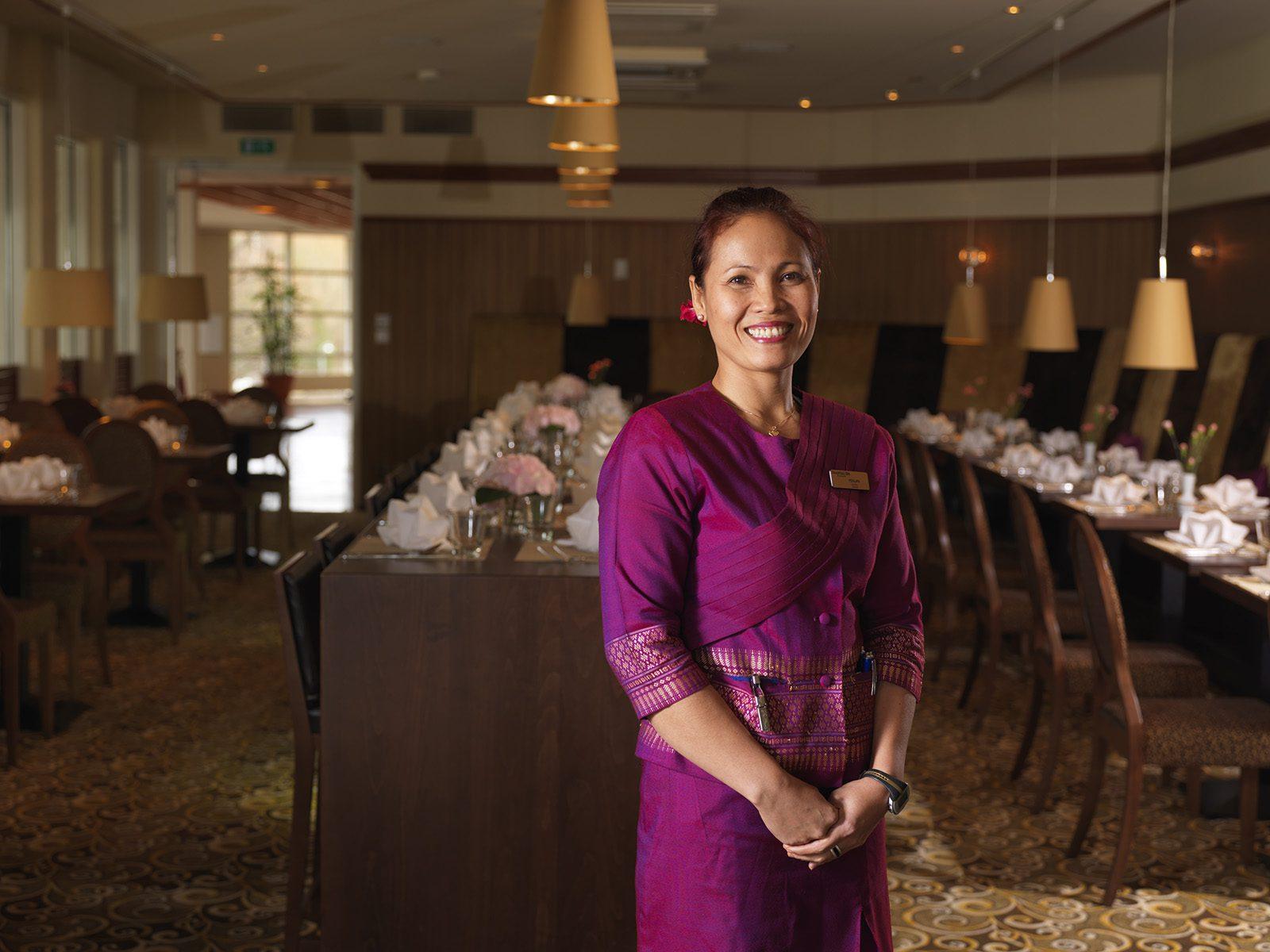Purppuraan thaimaalaiseen asuun pukeutunut tarjoilija hymyilee Thai Garden -ravintolassa.