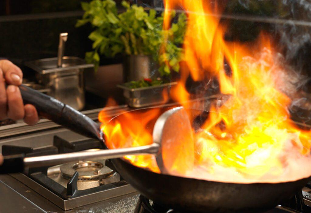 Ravintolan keittiö ja pannu, jonka sisältö liekehtii.