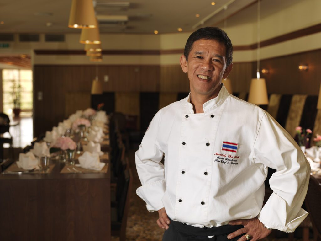 Thaimaalainen mieskokki hymyilee Thai Garden -ravintolassa.