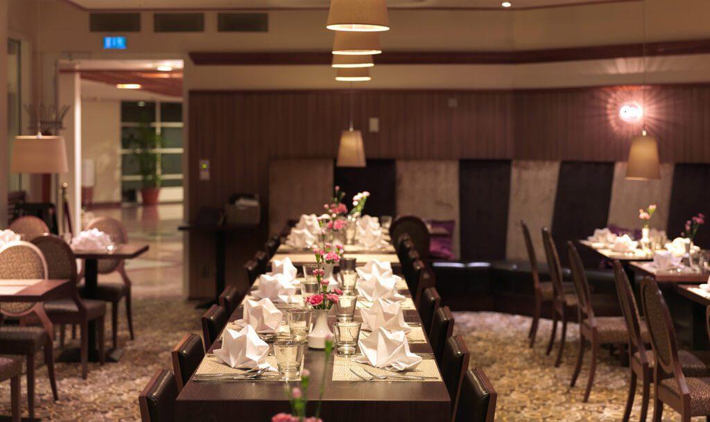 Thai Garden ravintolan sali, pitkä pöytä, joka katettu kauniisti. Pöydällä on vaaleanpunaisia kukkia maljakoissa.