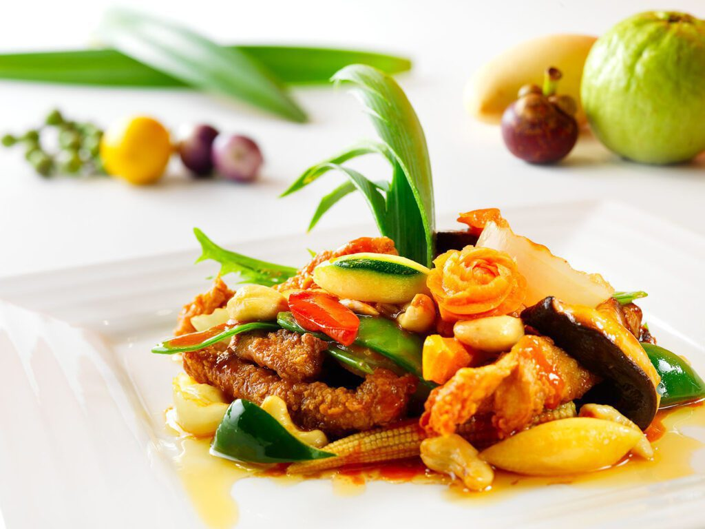 Thai Garden ravintolan annoskuva, jossa lihaa, minimaissia ja koristeellisesti leikattuja vihanneksia.