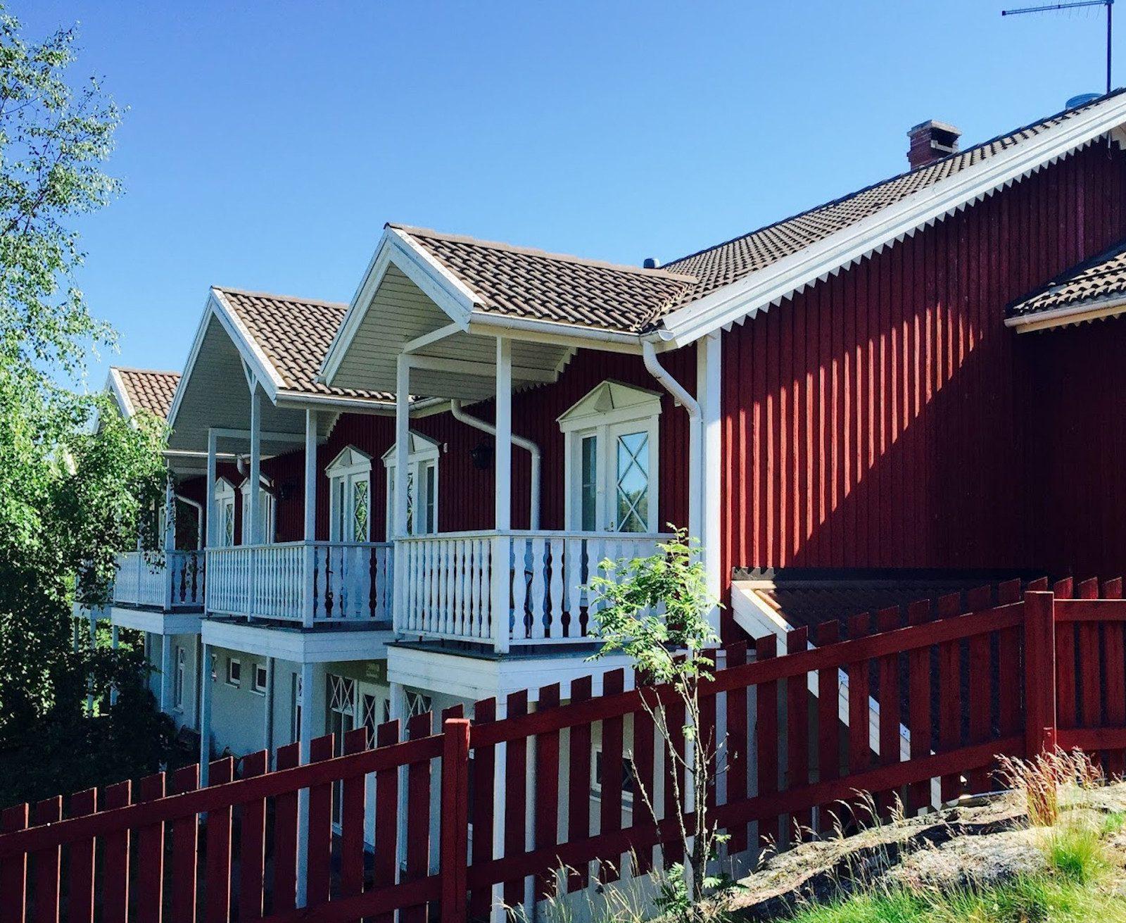 Punainen Saaristohotellin hotellirakennus, jossa kolme parveketta valkoisilla kaiteilla.