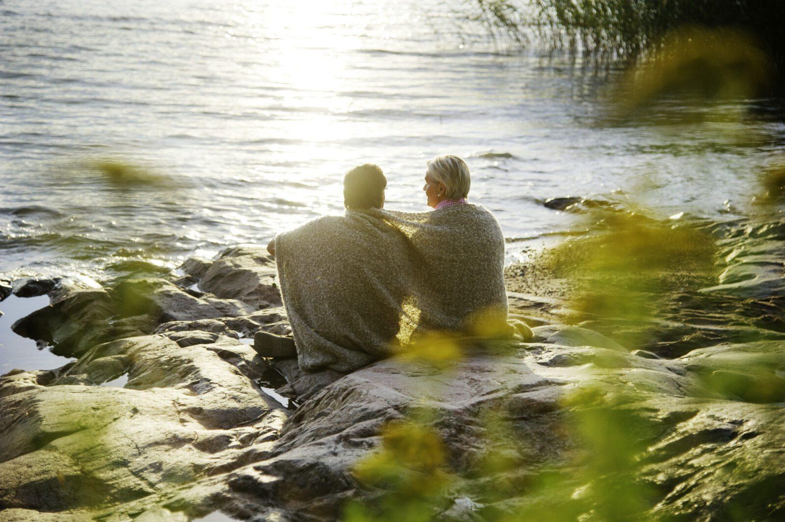 Pariskunta istuu rannalla viltin alla Naantalissa.